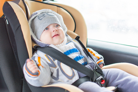 baby sitting in the car, fastened in a safe chair