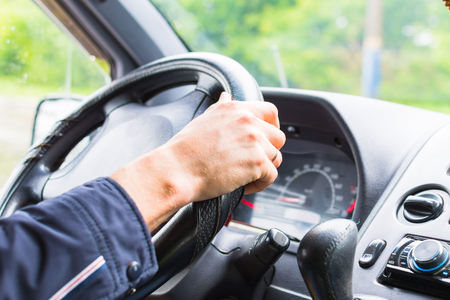 men's hand on the steering wheel of the car close-up