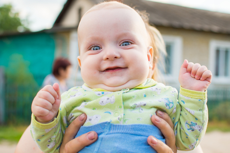 baby smiling in the arms of mother in outdoor in summer