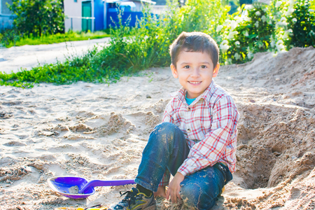 smiling boy with dark hair playing in the sand