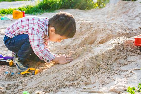 chłopiec 4 lata bawi się piaskiem Zdjęcie Seryjne