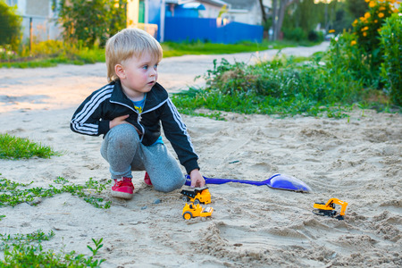 boy 3 years old blond playing with a car on the ground