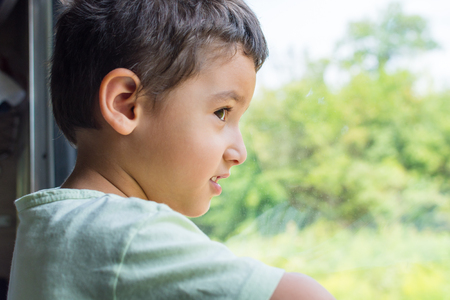 brunette boy looks at the window of the train with interest Stock Photo