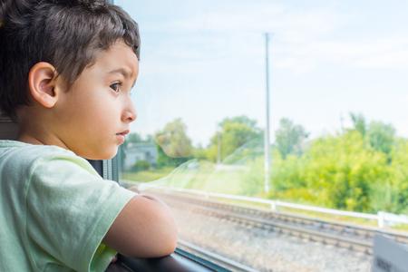 brunette boy looks sad from the train window