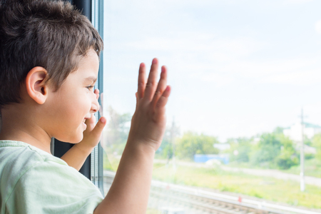 cheerful boy looks out the window of the train. Travel by rail