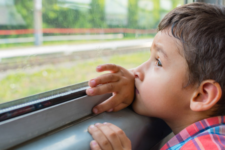 sad boy rides a train and looks out the window Stock Photo