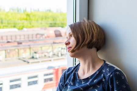 sad young woman sitting on the windowsill. From the window you can see the train
