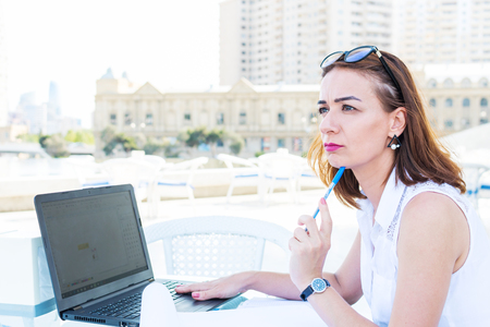 thoughtful business woman sitting in a summer cafe with a laptop