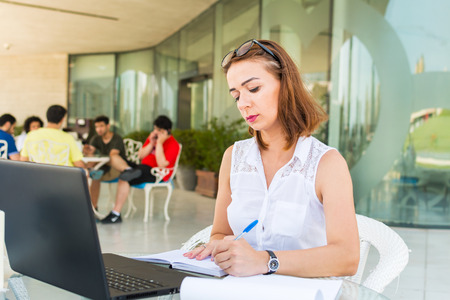 young business woman in summer outdoor cafe working in laptop Stock Photo