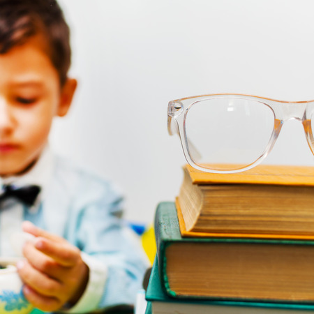 glasses on a stack of books, boy in the background blurred. Stock Photo