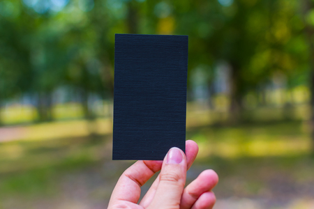 vertical black blank business card in hand outdoors