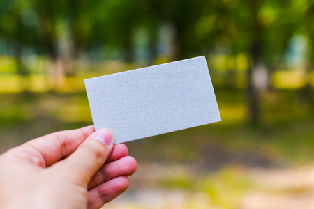white blank business card in hand outdoors