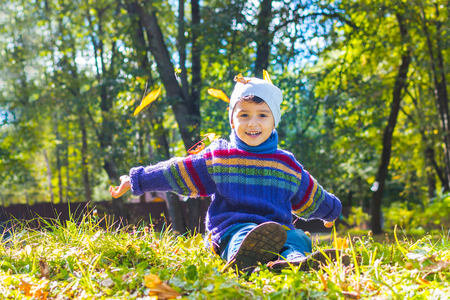 boy in sweater and hat sitting on the grass