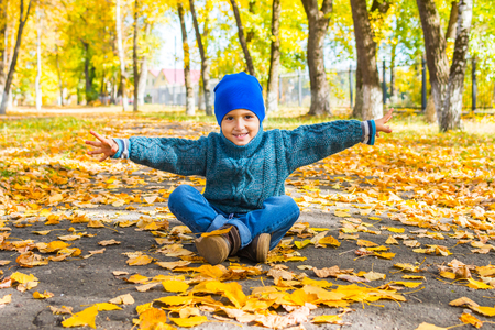 smiling boy in a hat and sweater sitting on the track in the Park in the fall. Yellow leaves everywhere