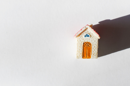 Small toy house with space for text on white background
