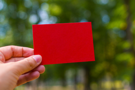 red blank business card in hand outdoors Stock Photo