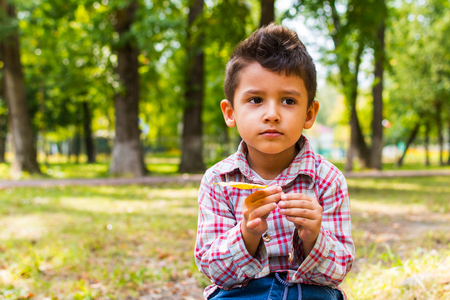 boy sitting on a log in the Park with a yellow leaf