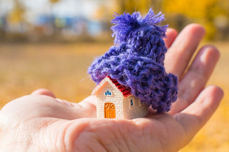 house with knitted hat in hand. concept