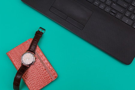 on the desktop laptop and notebook with a wrist watch