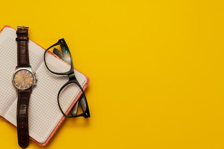 Notepad, glasses and clock on yellow background Stock Photo