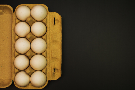 pack of chicken eggs on black background