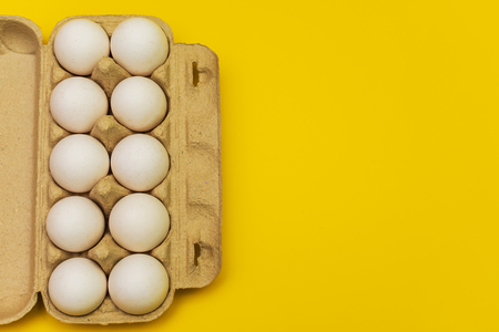 eggs in a cardboard box on a yellow background Stock Photo