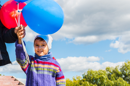 dad and son holding balloons outdoors Stock Photo
