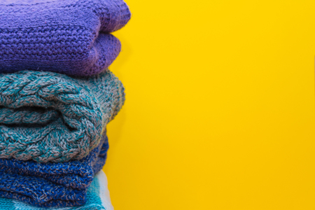 stack of knitted clothes on yellow background Archivio Fotografico