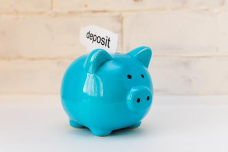 blue piggy Bank with an inscription Deposit on a light background