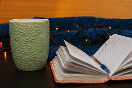 notebook and mug surrounded by garlands and sweaters