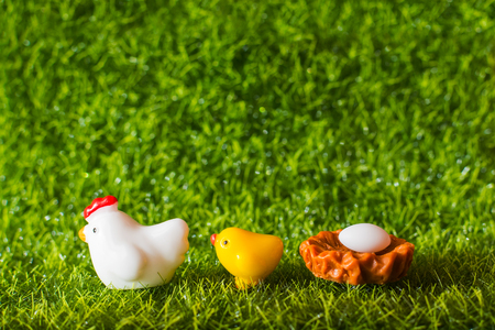 figures of chicken, chick and egg on the grass. concept Stock Photo