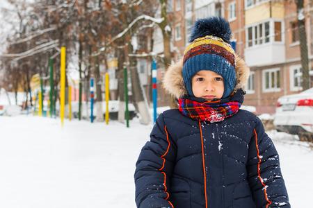 chłopiec spaceruje zimą na dworze