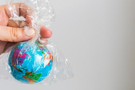 pequeño globo de la Tierra en una bolsa de plástico. El concepto de la Tierra pura Foto de archivo