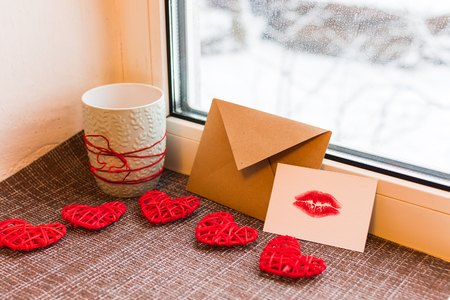 Cup, Kraft envelope, card with lip print and hearts on the windowsill. concept of Valentines day