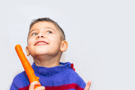 brown-eyed boy with carrots on a light background