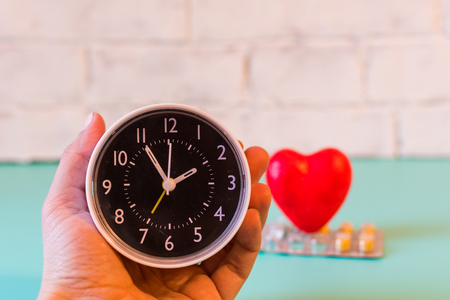 clock in hand on the background of blister of tablets and heart