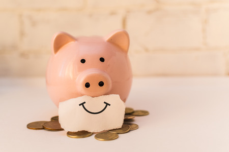 pink piggy Bank smiling with coins. concept of positive