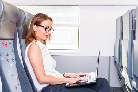young business woman working with laptop in the train
