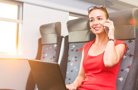 business woman talking on the phone and working with a laptop on the train Stock Photo