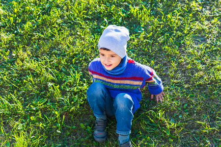 cheerful boy in a hat and sweater sitting on the grass