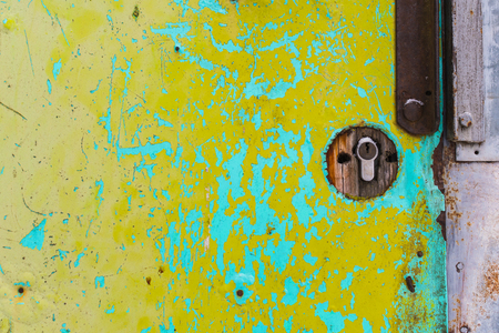 part of old shabby yellow door with a lock