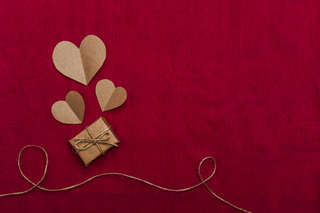 gift and hearts of craft paper on crimson background Stock Photo