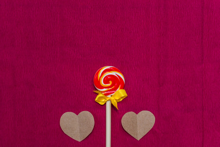 candy and two hearts of paper on a crimson background Stock Photo