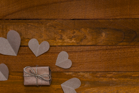gift and hearts of craft paper on wooden background Stock Photo