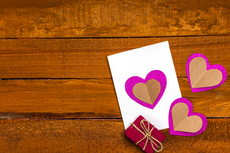 postcard with your own hands and a gift on a wooden background