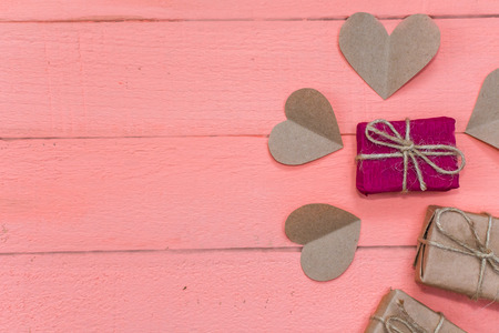 gifts and hearts of craft paper on pink background Stock Photo