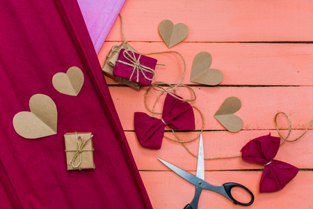 gifts and hearts on pink background. the process of packing gifts Stock Photo