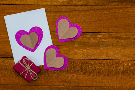 hand made postcard and a gift on a wooden background