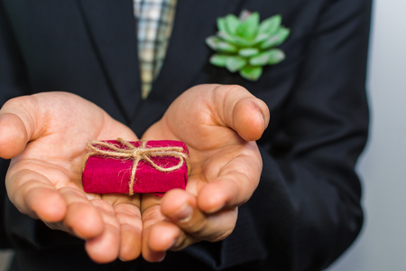 boy in a suit holding a gift box Stock Photo