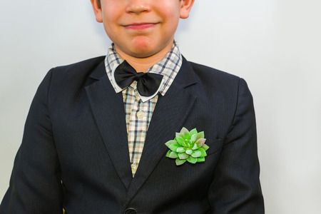 boy in a suit with a plant in his pocket. the emphasis on the suit